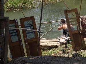 Lady washing hair in river in Myanmar behind closed doors