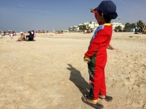 boy from behind pointing at high rises at Jumeira Beach, traveling with kids