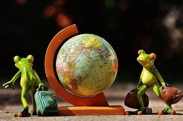 Globus und 2 Frösche, die einen Koffer halten